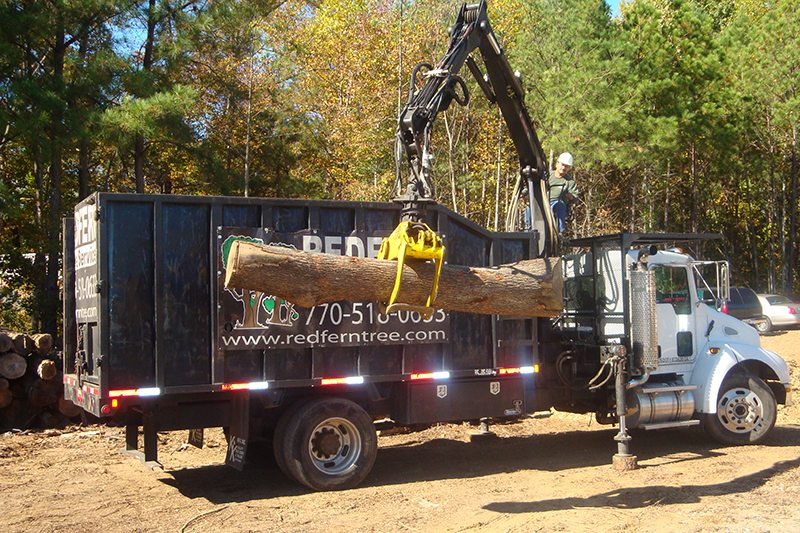 Log truck that uses the boom/grapple to remove logs from the property.