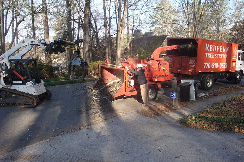 Crew hard at work using the bobcat T-190 to insert logs into the chipper.