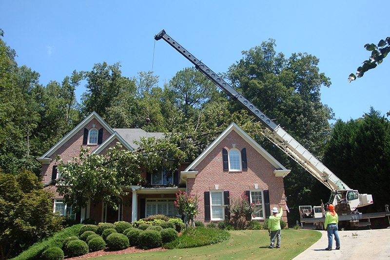 Crane work to remove a broken, fallen tree off of a customer's home.